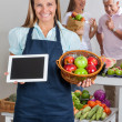 Saleswoman Holding Digital Tablet And Fruits Basket — Stockfoto