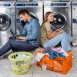 Couple Using Laptop And Earphones At Laundry — Stock Photo