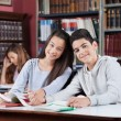 Girlfriend And Boyfriend Holding Hands At Table In School Librar — Stockfoto