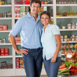Stock Photo: Couple Standing Against Shelves In Store