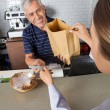 Salesman Collecting Cash While Passing Grocery Bag To Customer — Stock Photo