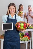 продавщица холдинг цифрового планшета и корзина с фруктами — Стоковое фото