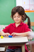 Boy Molding Clay At Desk — Stock Photo