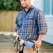 Stock Photo: Carpenter With Digital Tablet And Hammer In Tool Belt At Site