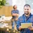 Manual Worker Holding Digital Tablet With Coworker Standing In B — Stock Photo #34166447