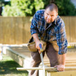Manual Worker Sawing Wood At Construction Site — Stock Photo