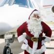 Santa With Hands On Hip Against Private Jet — Stock Photo