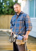 Carpenter With Digital Tablet And Hammer In Tool Belt At Site — Stock Photo