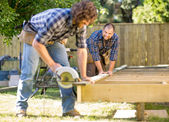 Carpenter Looking At Coworker While Assisting Him In Cutting Woo — Stockfoto