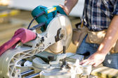 Carpenter Cutting Wooden Plank With Table Saw At Site — Stock Photo