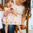 Girl Eating Cupcake While Sitting On Mother's Lap — Stock Photo #34193483