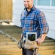 Worker With Digital Tablet And Hammer In Tool Belt At Site — Stock Photo