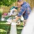 Worker Cutting Wood Using Table Saw At Site — Stock Photo