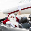 Santa Waving Hand In Convertible Against Private Jet — Stock Photo