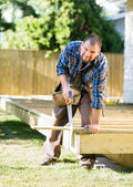Mid Adult Worker Cutting Wood With Saw At Construction Site — Stock Photo