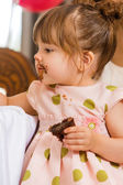 Girl Eating Cake With Icing On Her Face — Stock Photo