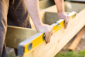 Carpenter's Hands Checking Level Of Wood At Site — Stockfoto