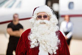 Santa Standing Against Private Jet — Stock Photo