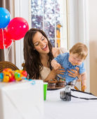 Mother Holding Boy With Messy Hands Covered With Cake Icing — Stock Photo
