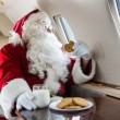 Santa Holding Cookie While Looking Through Private Jet's Window — Lizenzfreies Foto