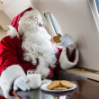 Santa Holding Cookie While Looking Through Private Jet's Window — Stock Photo