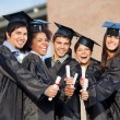 Students In Graduation Gowns Showing Diplomas On Campus — Stock Photo #34248655