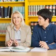 Stock Photo: Confident Teacher With Student Looking At Her In Library