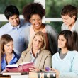Professor And Students Discussing Over Book In Classroom — Stock Photo