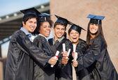 Alunos em vestidos de formatura, mostrando os diplomas no campus — Fotografia Stock
