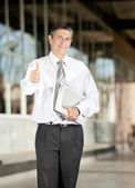Confident Teacher With Books Gesturing Thumbsup On Campus — Stock Photo