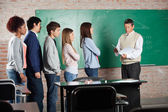 Professor With Exam Results While Students Standing At Desk — Stock Photo