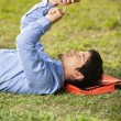 Stock Photo: Student Text Messaging On Mobilephone While Lying At Campus