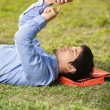 Student Text Messaging On Mobilephone While Lying At Campus — Stock Photo #34250493