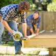 Carpenter Cutting Wood With Handheld Saw While Coworker Helping — Stock Photo #34250599