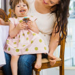 Birthday Girl Eating Cupcake While Sitting On Mother's Lap — Stock Photo #34251051