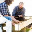 Stock Photo: Carpenter Communicating With Coworker Measuring Wooden Frame