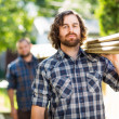 Stock Photo: Carpenter With Coworker Carrying Wooden Planks Outdoors