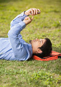 Student Text Messaging On Mobilephone While Lying At Campus — Stock Photo