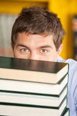 Student Peeking Over Piled Books In University Library — Stock Photo