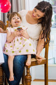 Birthday Girl Eating Cupcake While Sitting On Mother's Lap — Stock Photo