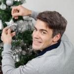 Happy Man Decorating Christmas Tree — Stock Photo
