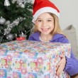 Girl Holding Gift By Christmas Tree — Stock Photo