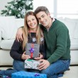 Loving Couple With Christmas Gifts At Home — Stock Photo