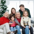 Stock Photo: Family With Christmas Present In House