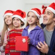 Family In Santa Hat With Christmas Present — Stock Photo #34275613