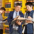 Stock Photo: Librarian Assisting Student In College Library