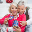 Surprised Senior Woman With Man Looking At Christmas Gift — Zdjęcie stockowe