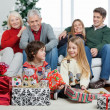 Children With Christmas Presents While Family Sitting On Sofa — Stock Photo