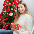 WomWith Gift Sitting By Christmas Tree — Stock Photo #34276733