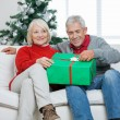 Couple With Christmas Gift Sitting On Sofa — Φωτογραφία Αρχείου